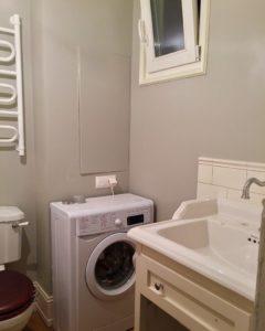 Стиральная машина в ванной комнате у стены